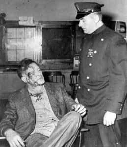 Tierney Jailed After Scuffle New York -- Patrolman Louis Romano questions former movie actor Lawrence Tierney in the West 54th Street Police Station early today. Tierney was arrested after a bruising battle with Romano and another policeman on Sixth Avenue after they had ejected him from a bar. All three were given treatment at a hospital and released. (1958)